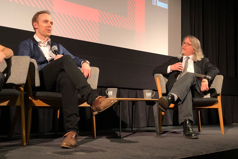 Two men engaged in a conversation sit on a stage.