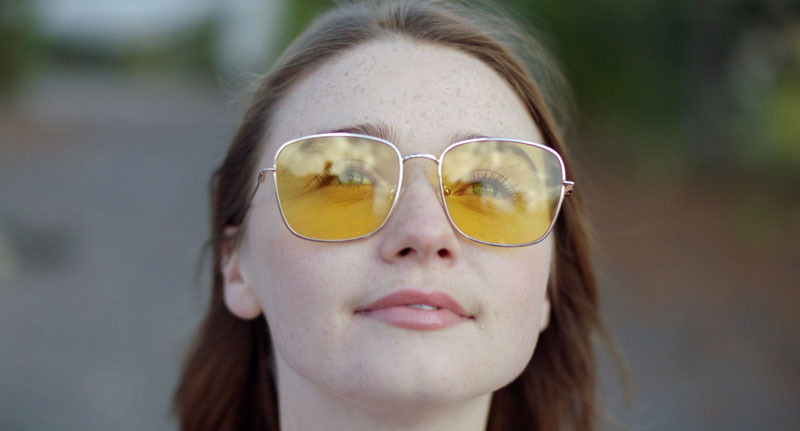 A young woman wears sunglasses with yellow lenses and looks up at the sky.