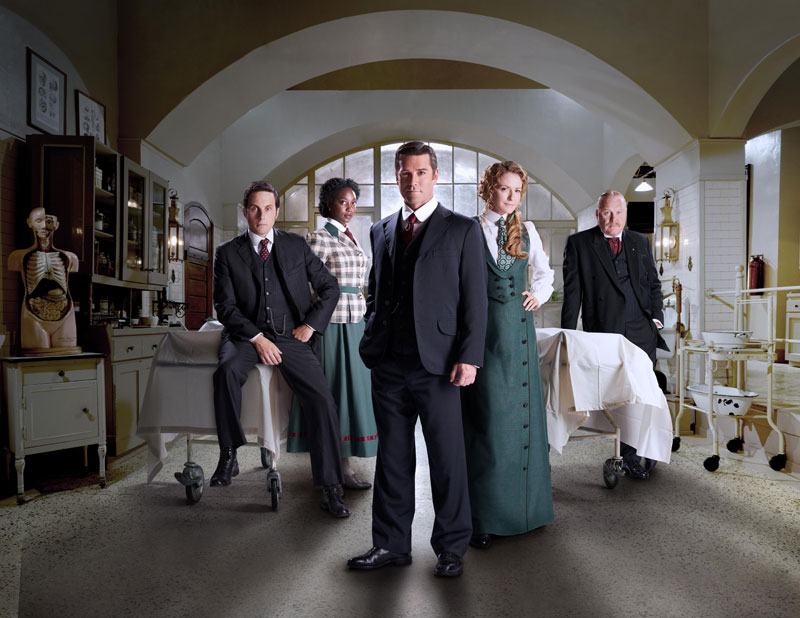 Five actors pose for a photo on set of a period mystery drama TV series