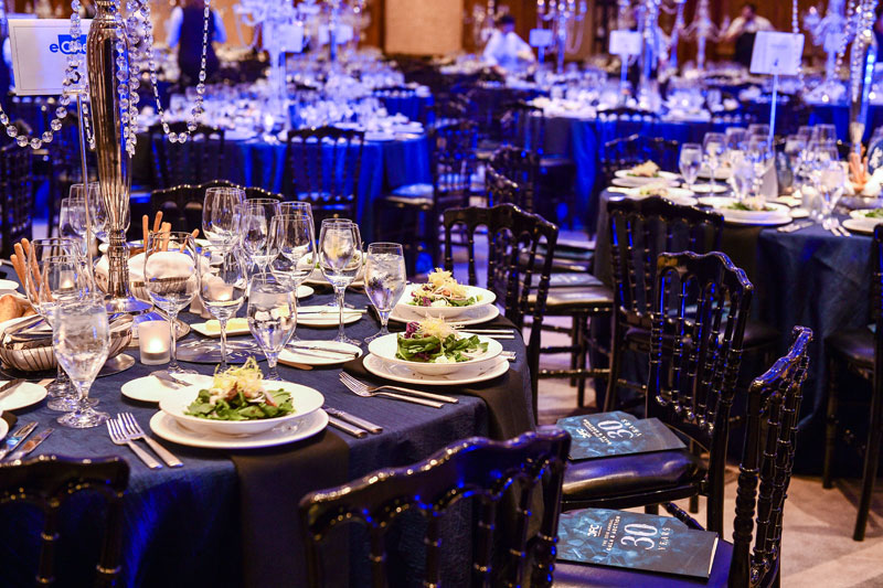 Tables inside a ballroom decorated for a gala.