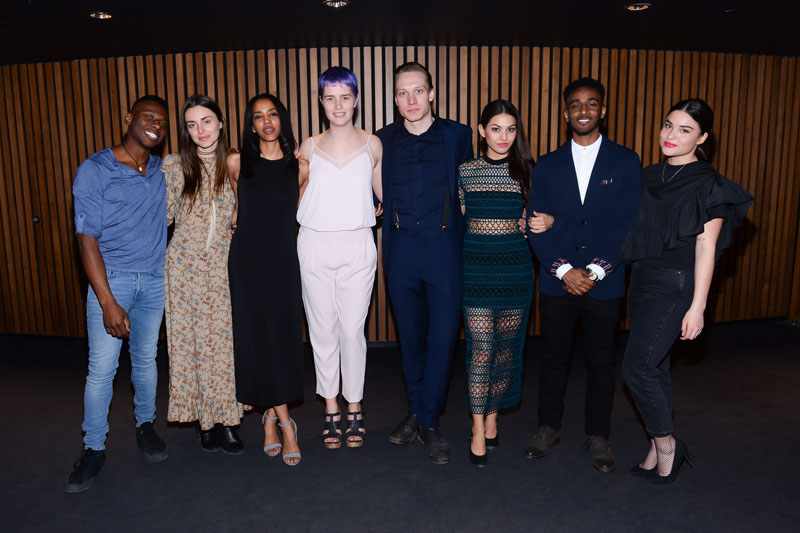 Eight actors standing side-by-side posing for a photo.
