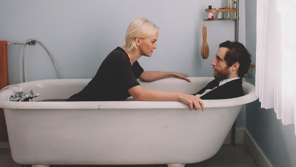 A woman faces a man as they sit in a bathtub fully clothed.