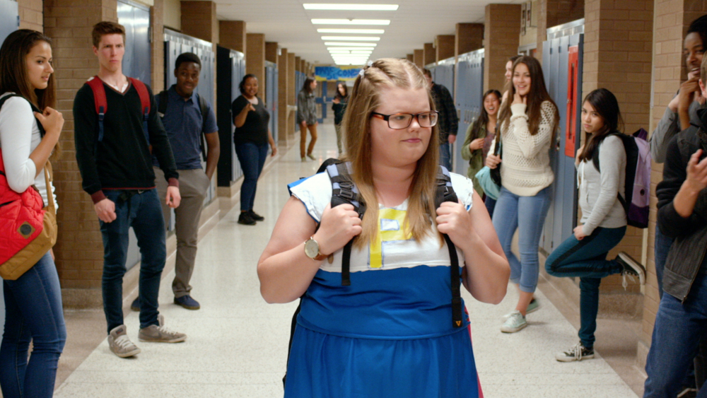 A teenager wearing a cheerleading outfit walks through the halls of her high school