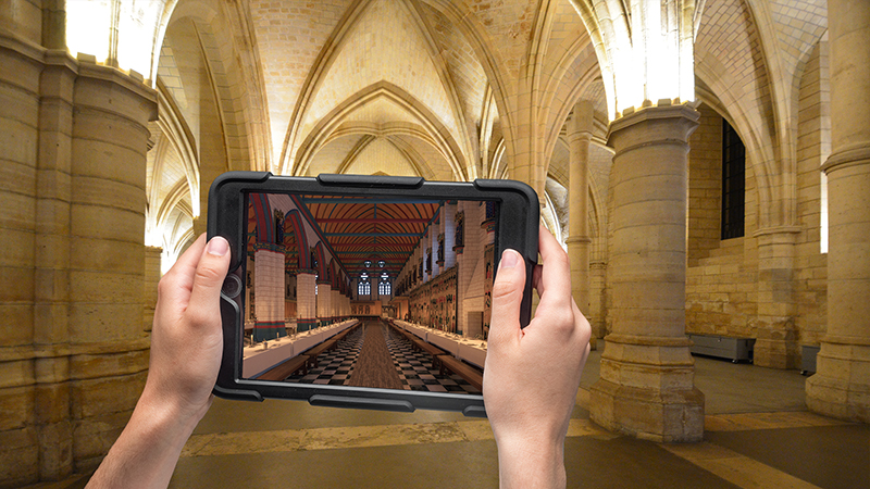 A person's hands hold up an ipad. The ipad screen shows an augmented reality view that transforms the bare, palatial room in which the person stands into a more opulent, decorated grand hall.