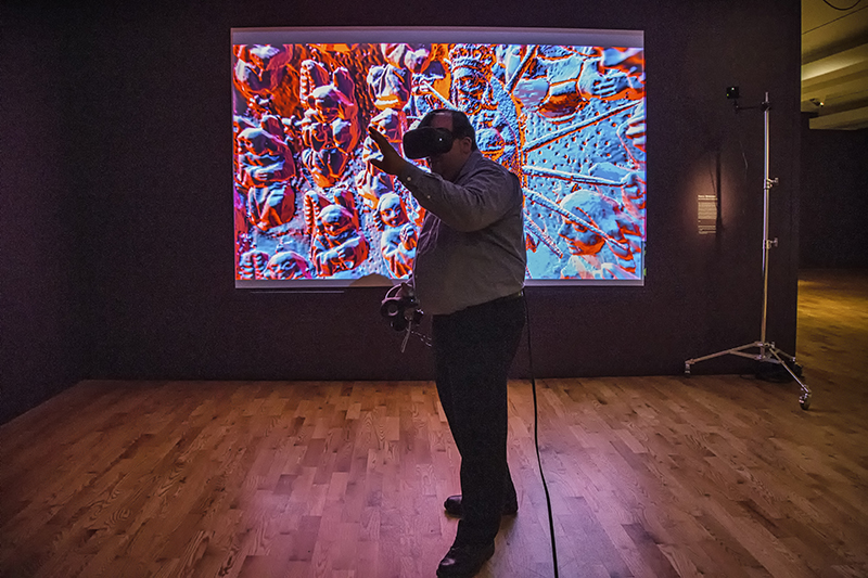 A man stands in VR gear in an art gallery, arm outstretched, with a VR projection on the screen behind him.