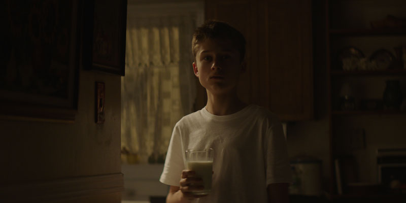 A boy holding a glass of milk.