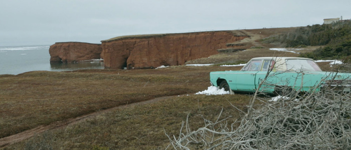 A car is parked near a cliff