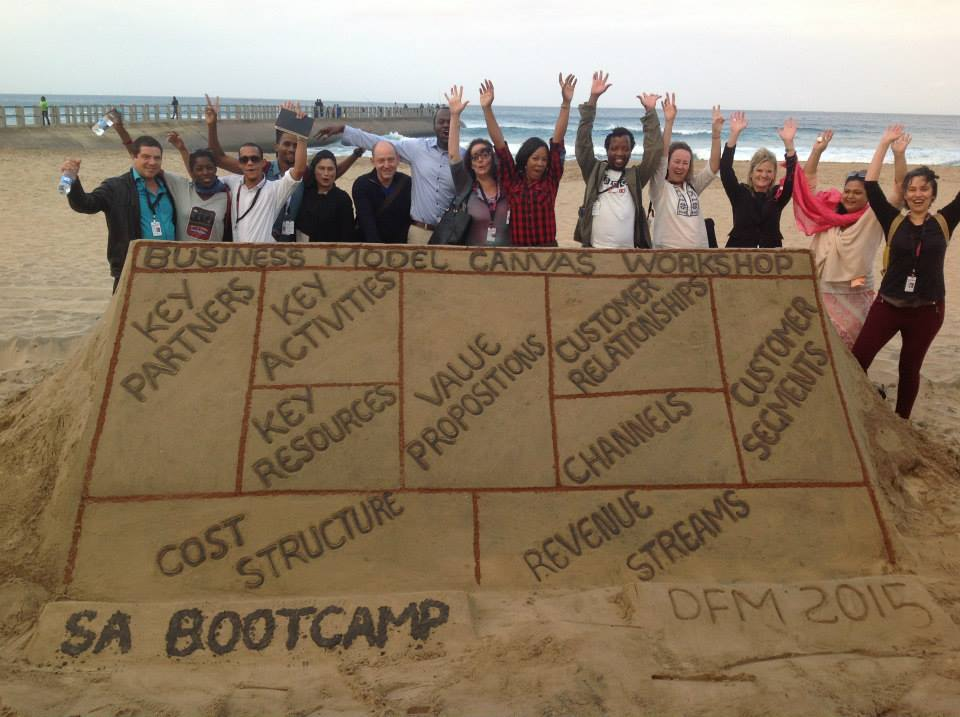 Group of people on the beach standing behind a large sand-made structure with their hand in the air. The structure is flat and rectangular and outlines a chart titled 'Business Model Canvas Workshop'.