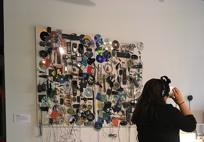 Woman in a VR headset, standing in front of an artwork hanging on the wall, a piece composed of items of digital debris like TV remotes.