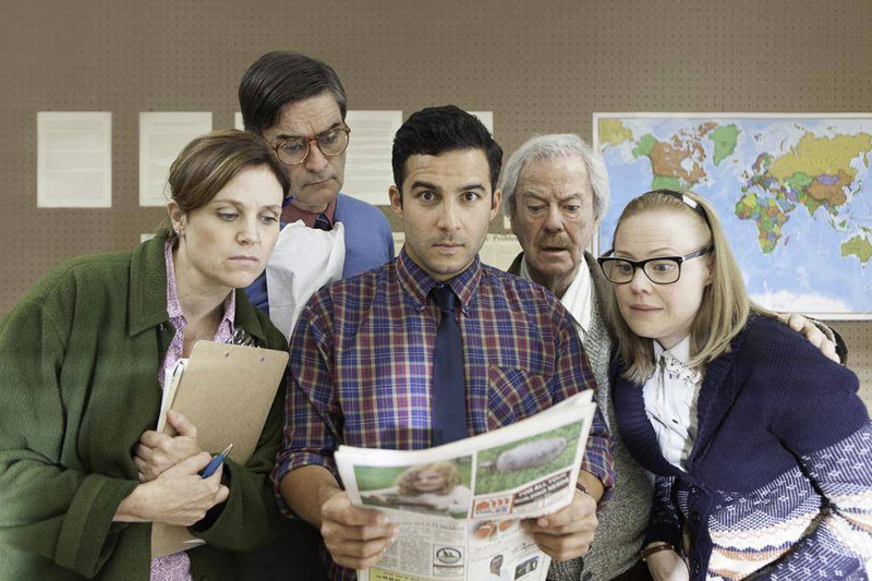 Five people stand around one newspaper