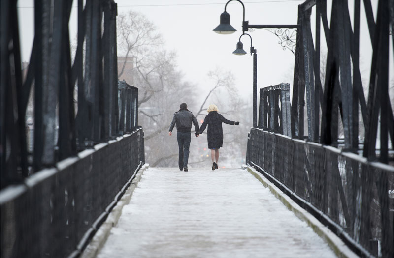 two people walk on a snowy bridge