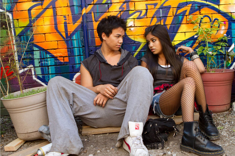 Two young people look at each other while sitting next to one another in front of a wall with graffiti art
