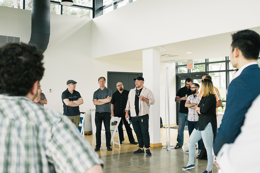 A group of people standing in a room. At the center of the photo is a man in a black baseball cap. The man looks like he is speaking while the others in the image are turned towards him.