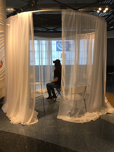 A woman sitting in a sheer-curtained, semi-shrouded space, while she wears a VR headset.