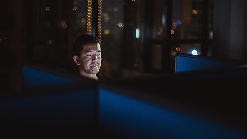 A man sitting in a dark space, on an upper floor of a high rise, his face illuminated by the glow of the computer screen at which he is gazing.