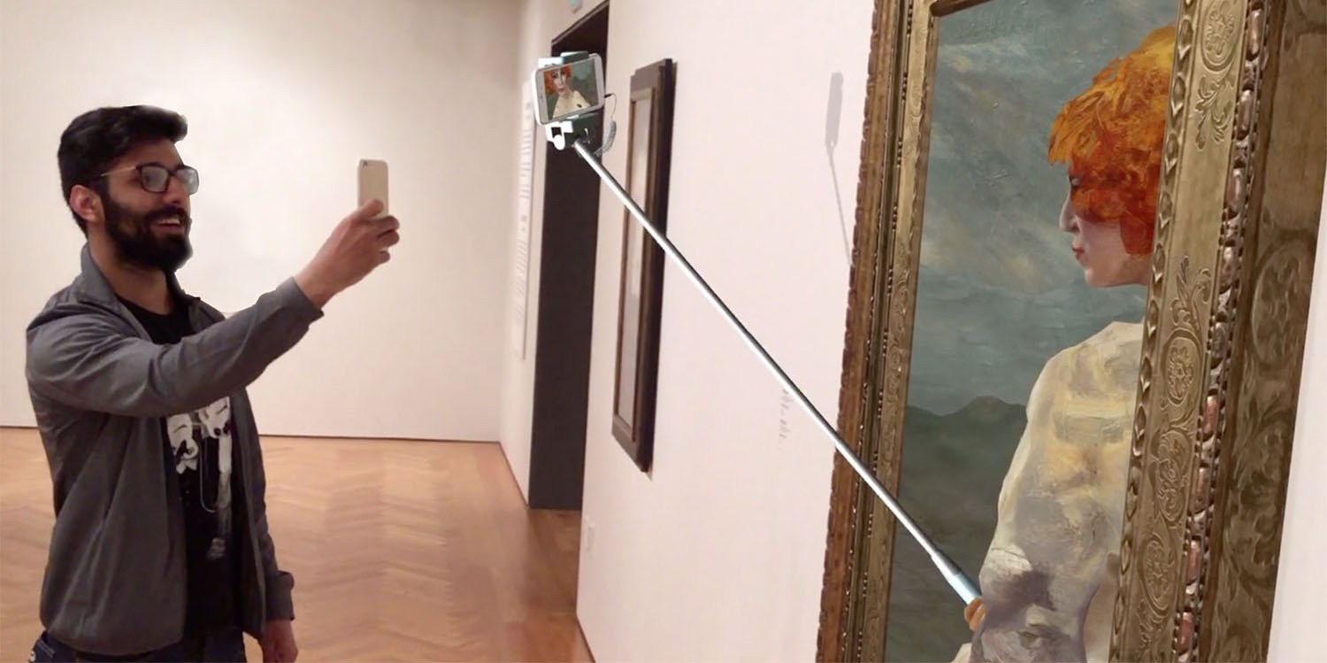 A man holds his phone up to a framed painting to take a photo. The woman in the painting is holding up a selfie stick and taking a photo of herself.