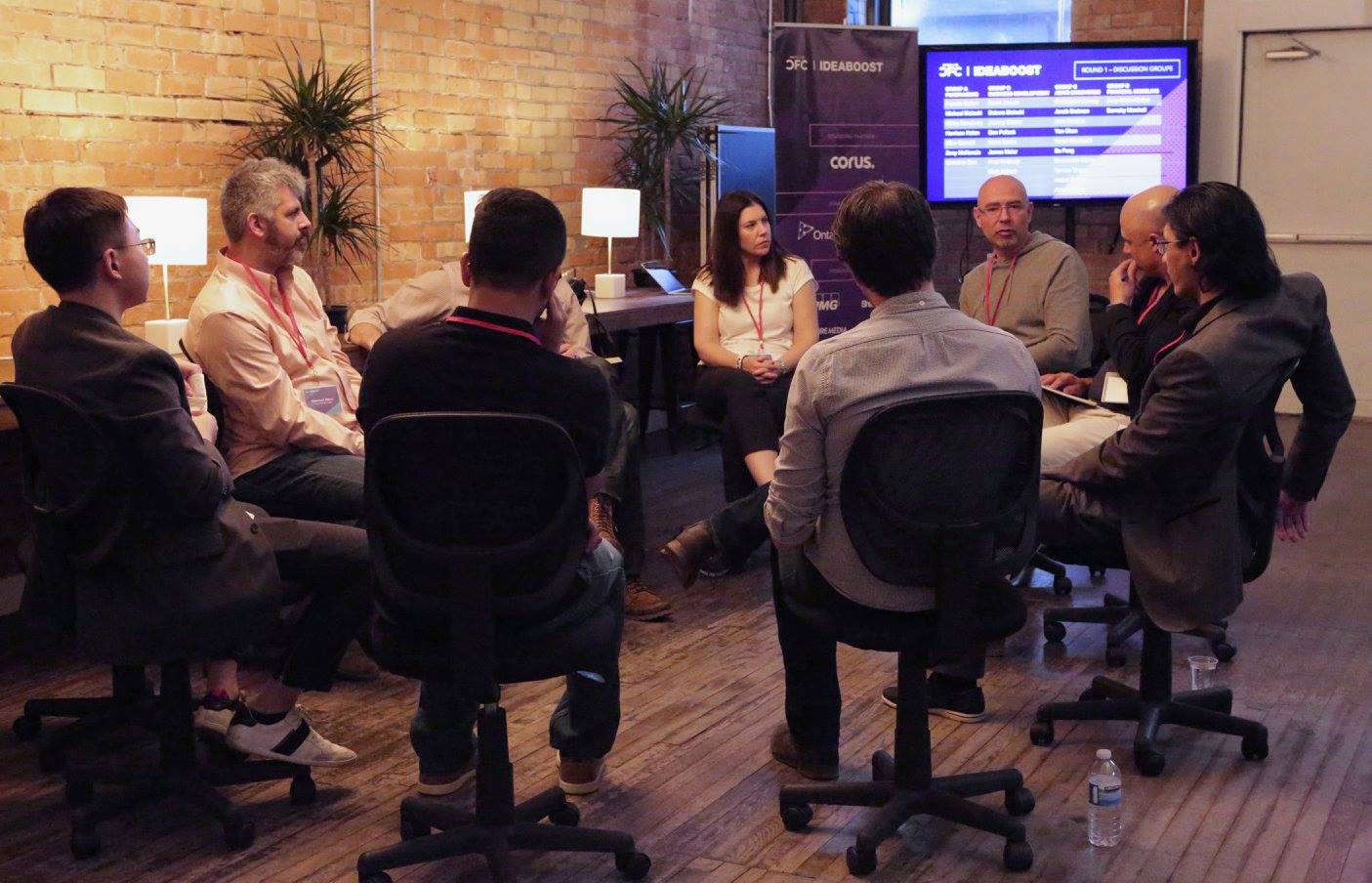A group of people in a circle formation. They are all sitting in office chairs and facing each other.