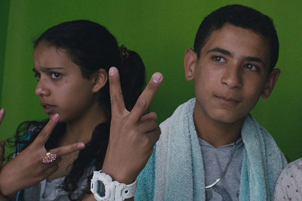 Two young people making peace signs with their fingers