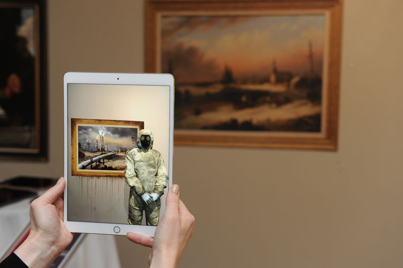 A person's hands, seen holding up an iPad in front of a painting, with the ipad in focus.