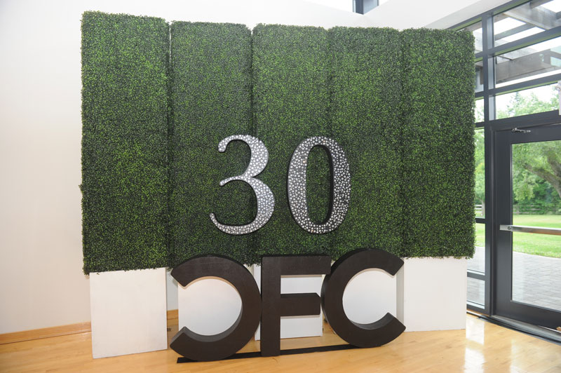 "A tall wall made out of greenery, with the block letters ""30 CFC"" in front of it."
