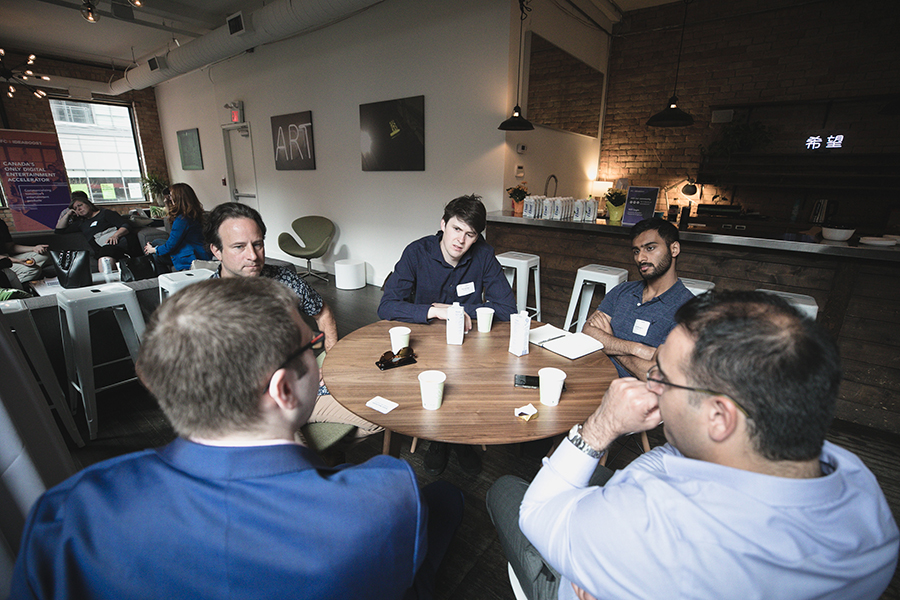 Five people sitting around a round table.