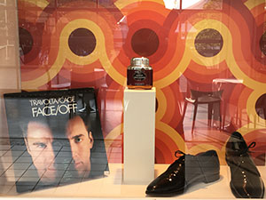 In a glass exhibition case stands a laserdisc, flask and pair of shiny black shoes.