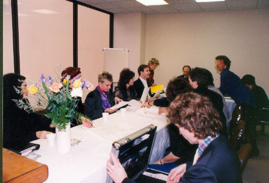 A group of people gather in a board room