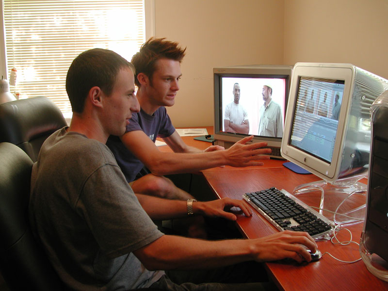 Two individuals sit in an edit suite for a film