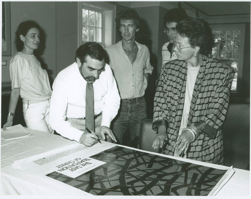 A movie director signing a poster for one of his films