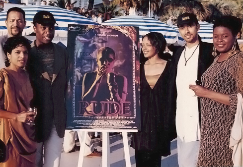 Six individuals pose beside a film poster for a premiere at Cannes Film Festival