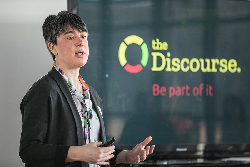 A woman talking and standing next to a tv screen. On the screen is a logo for 'The Discourse'.