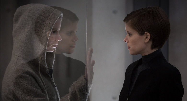 Two women standing face to face and between them is a glass wall.