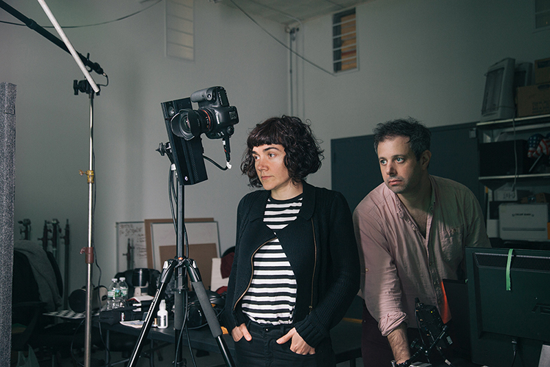 A woman and man stand next to a film camera in a studio.