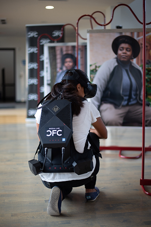 A woman in a VR headset/backpack, crouching mid-experience, with photos blurred out in front of her.
