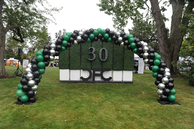 "An arching banner of green, white and black balloons outside, with a display of boxwood and the words ""CFC 30"" on it."