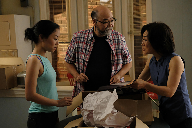 A father, mother and teenage daughter stand around a table opening a box and talking.