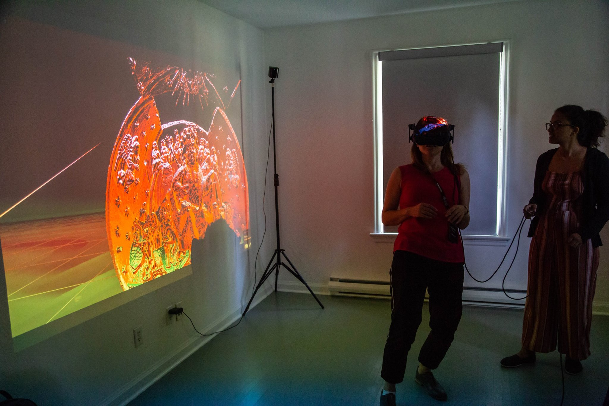 A woman wears a VR headset while another woman stands next to her and holds a wire connected to the headset. On the left is a projection displaying a 3D rendering of a gothic bead.