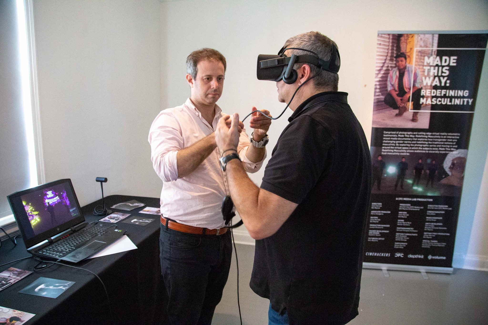 One man wearing a VR headset. A man stands next to him holding a wire connected to the headset.