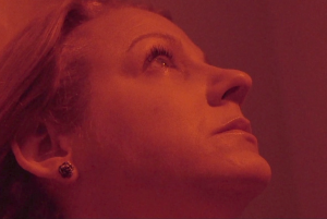 A woman's face in close-up looking up, in red light.