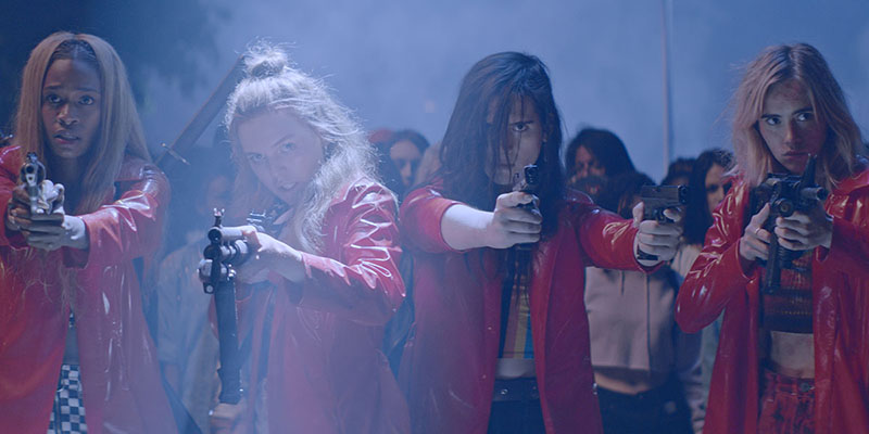 Four tough girls in shiny red jackets stand holding and pointing their guns at the camera.