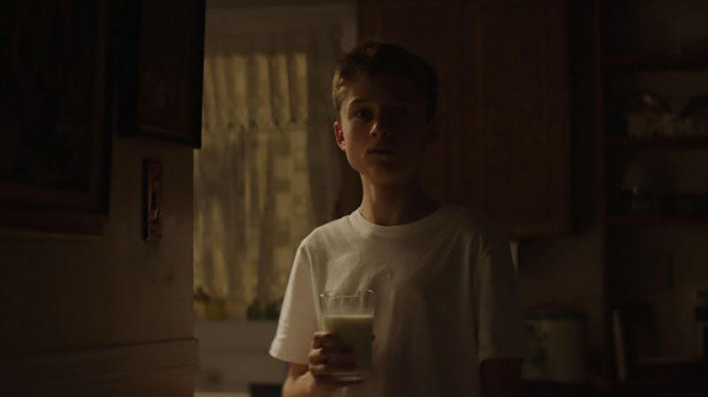 A young boy holding a glass of milk in a dark kitchen.