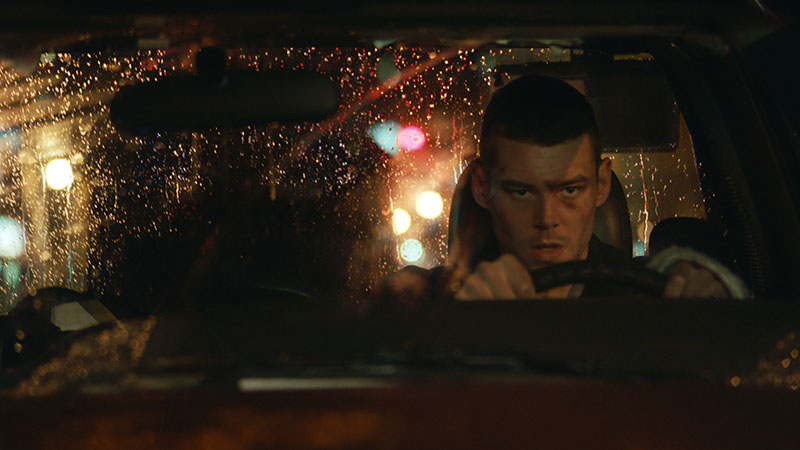 A determine man drives a truck on a rainy road at night.