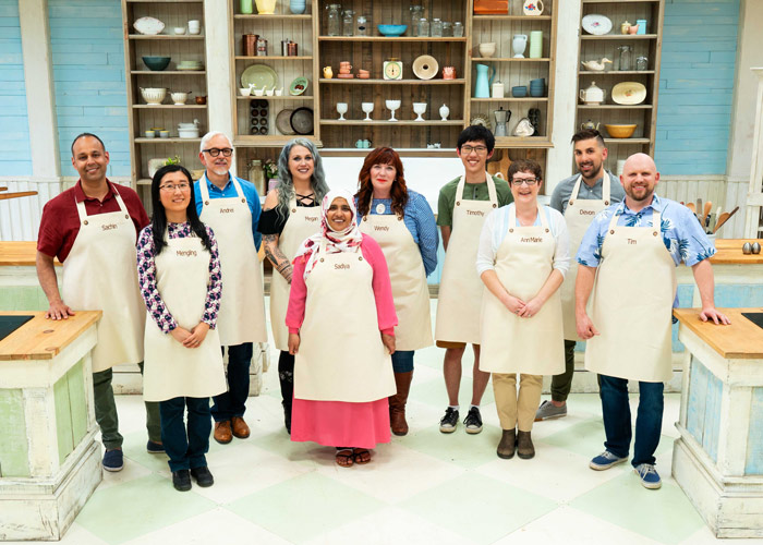 A group of ten bakers stand in a teal-coloured kitchen