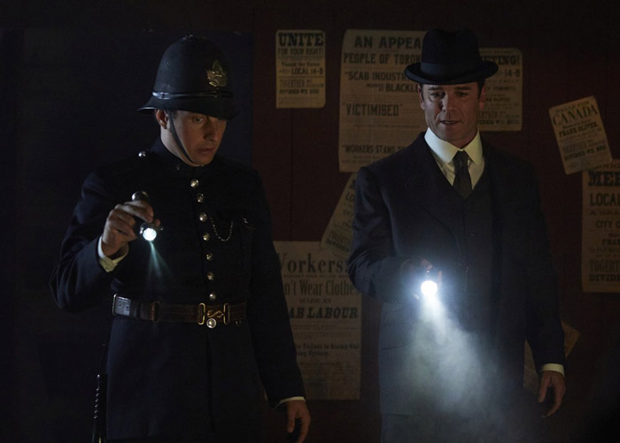 Two old-timey detectives shine flashlights in a dark alley