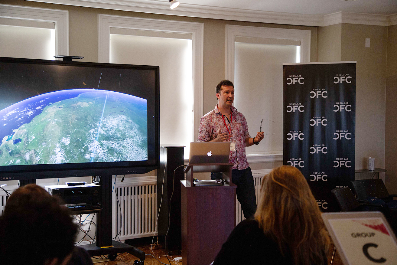 A man standing and talking in front of a podium. To his right is a large screen displaying an image of Earth.
