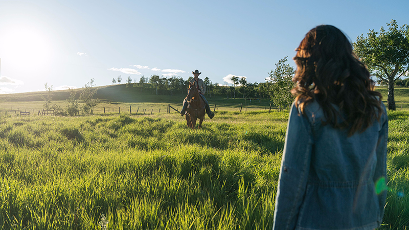 A woman faces a sunny green meadow, watching a man on a horse ride towards her.