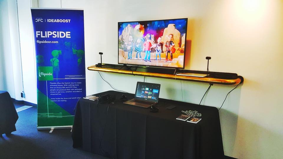 A VR demo set up with a large tv screen on top of a shelf. Below the shelf is a laptop on a long black table. Next to the table is a green pull-up banner.