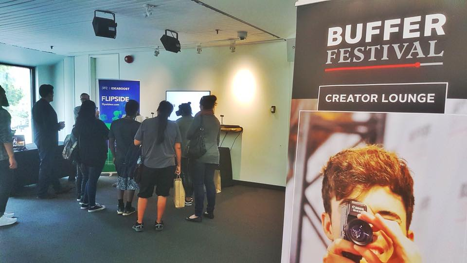 A group of people in a room standing in front of a tv screen. Behind them to the right is a pull up banner that reads 'Buffer Festival' and a subheading 'Creator Lounge'.
