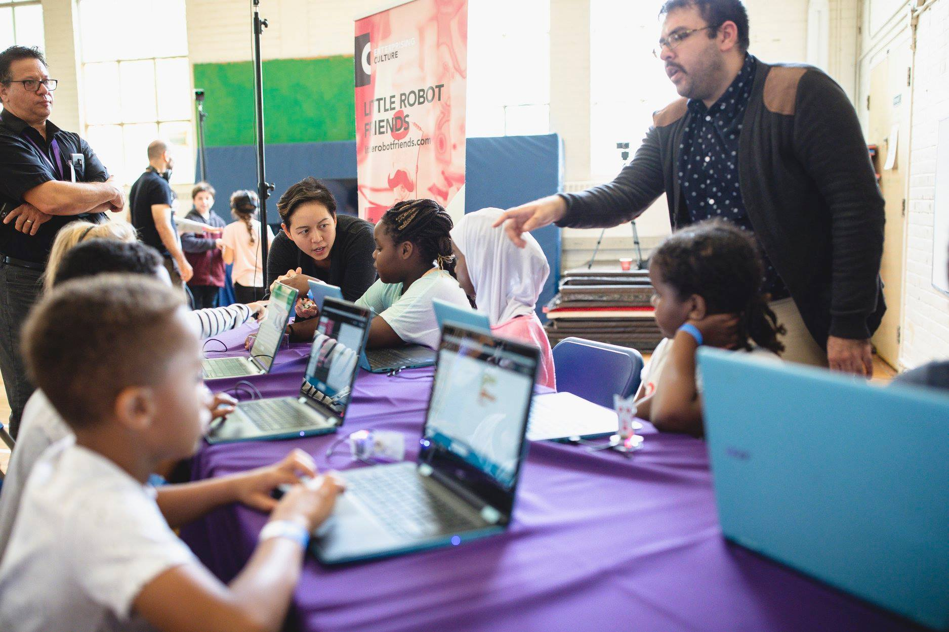 A group of kids sit along a purple table and in front of each of them is a laptop. One man stands behind of the table while a woman is at the end of the table talking to a girl.