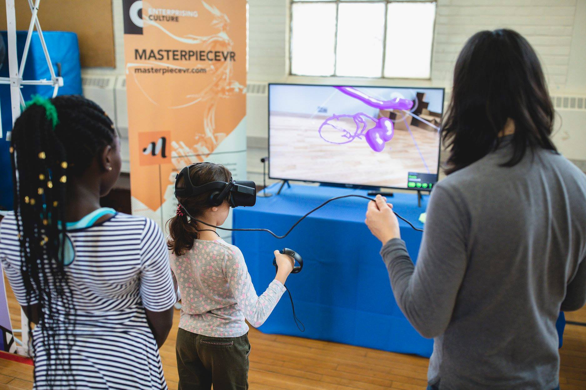 A girl stands in front of a tv screen while wearing a VR headset. Another girl stands behind her and a man stands next to them holding a cord connected to the headset.